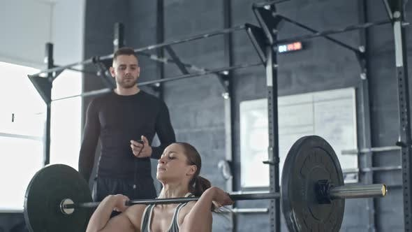 Thumbnail for Personal Trainer Controlling Woman Exercising with Barbell