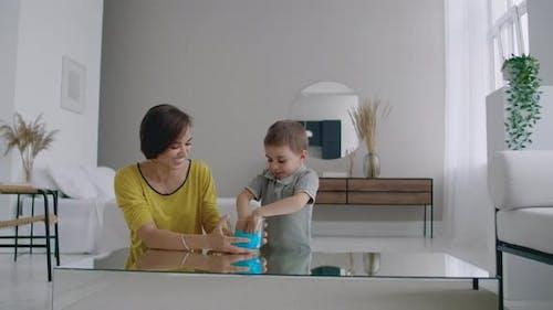Mama und Sohn sitzen auf dem Boden, spielen am Tisch und lachen mit einem elastischen Spielzeug