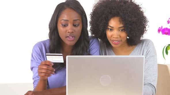 Two African American friends deciding what to buy online