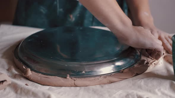 Thumbnail for Potter Forming Clay Into a Dish By Using a Form and Tools To Get the Perfect Shape