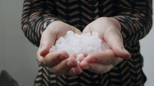 Hands with hail, the result of nasty weather