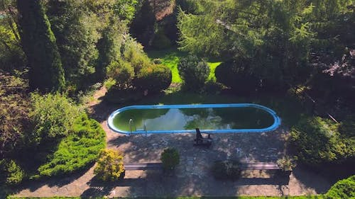 Old Abandoned Swimming Pool with Dirty Green Water. Flight Over a Beautiful Green Area with an