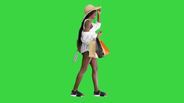 Thumbnail for Happy African American Woman in Straw Hat Walking with Shopping Bags on a Green Screen Chroma Key