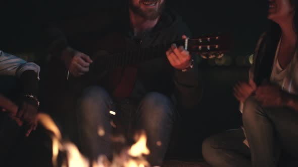 Thumbnail for Happy Man Playing Guitar for Friends at Campfire