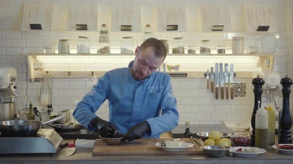 Thumbnail for Chef Man in Restaurant Uniform and Black Gloves Stand in the Modern Kitchen