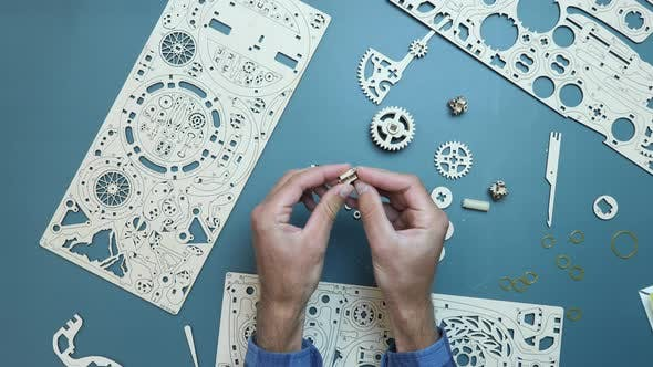 Game concept. Mechanical wooden puzzle toy. Man holding small toy pieces in hands