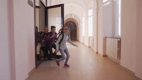 Heureux enfants qui ouvrent la porte et courent à travers le couloir