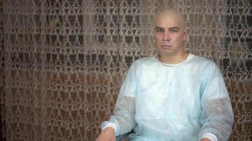 A Bald Young Man with Cancer Looks at the Camera and Cries. The Patient Covers His Face with His