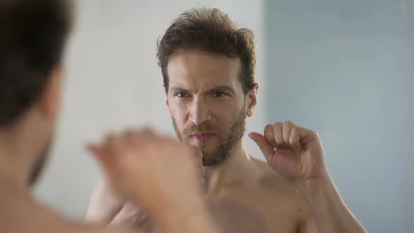 Guy kümmert sich um Mundhygiene, putzt seine Zähne jeden Tag mit Zahnseide