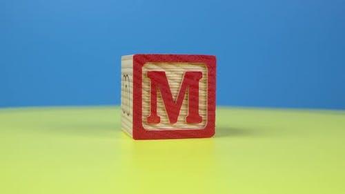 "Close up shot letter ""M"" alphabet wooden block"