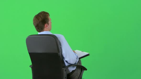Thumbnail for Businessman turning around in chair on greenscreen