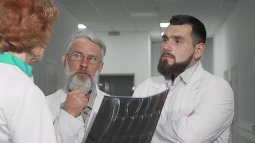 Two Male Doctors Discussing MRI Scan of a Patient with Their Female Colleague