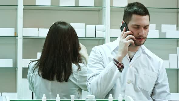 Thumbnail for Female and Male Pharmacists Working in Pharmacy, Talking Via Smart Phone and Checking Pills
