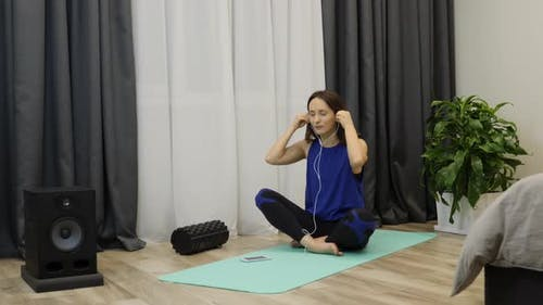 Female in earphones starts meditation sitting on yoga mat at home. Yoga and meditation concept