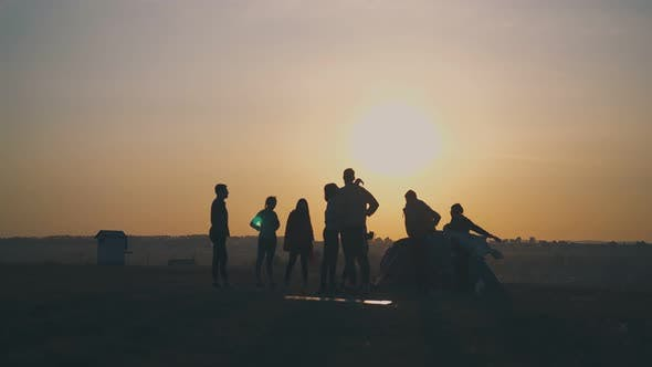Silhouettes of Tourists Spending Time By Tent at Sunset