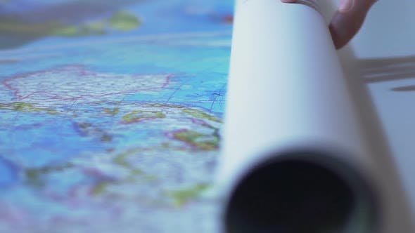 Thumbnail for Man Unrolling World Map on Table, Tourist Planning Route for Vacation Abroad
