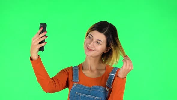 Cover Image for Young Woman Makes Selfie on Mobile Phone Then Looking Photos on Green Screen