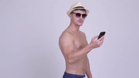 Cover Image for Muscular Bearded Tourist Man Looking for Directions with Phone