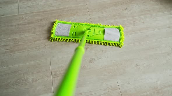 New green mop moving on parquet floor