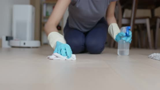 Housewife clean floor with rag and detergent
