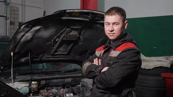 Technician with Crossed Arms Stands By Renovated Automobile