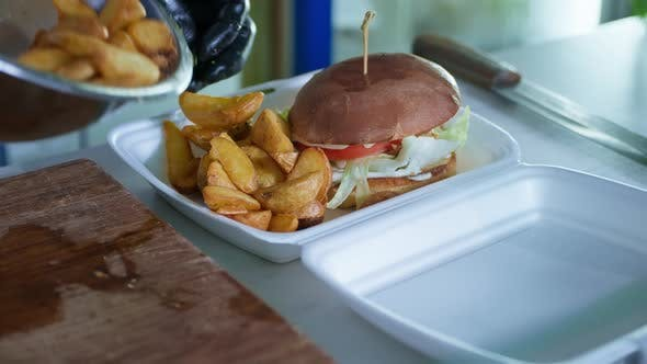 Takeaway Food, a Hot Juicy Burger with Fried Potatoes in a Package for Delivering Food From a Cafe
