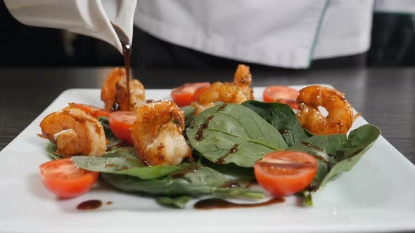 Thumbnail for Mediterranean Cuisine. Chef Pours Sauce Over Vegetarian Seafood Salad with Shrimps. Finishing Salad