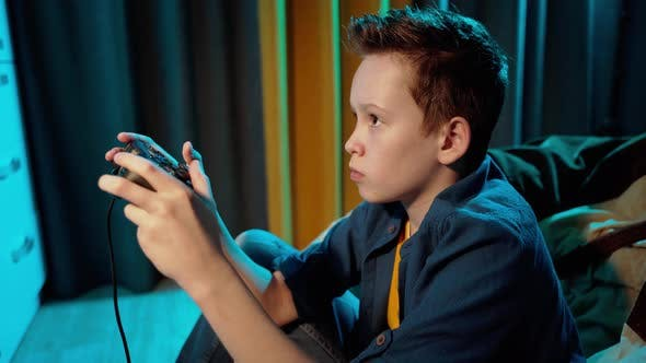 Cover Image for Concentrated boy playing video games in his room