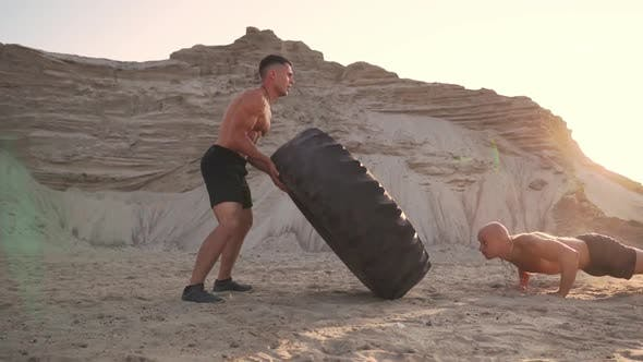 Cover Image for Two Athletes Train in Active Mode on the Beach Doing push-UPS and Pushing a Huge Wheel