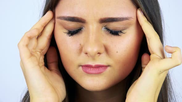 Thumbnail for A Young Beautiful Woman Has a Headache and Rubs Her Temples - Face Closeup - White Background