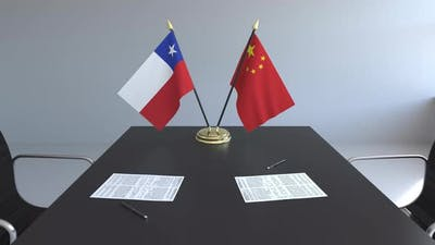 Flags of Chile and China and Papers on the Table