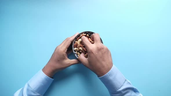 Thumbnail for Top View of Hand Holding a Bowl of Mixed Nut on Blue Background