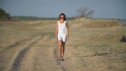 Girl in a White Dress Walks