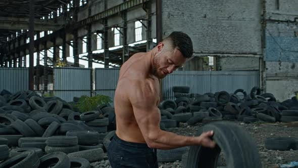 Thumbnail for Male athlete with tires in abandoned place