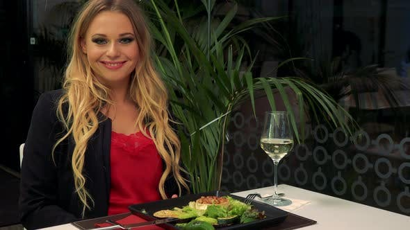Thumbnail for A Young, Beautiful Woman Sits at a Table in a Restaurant and Shows a Thumb Up To the Camera