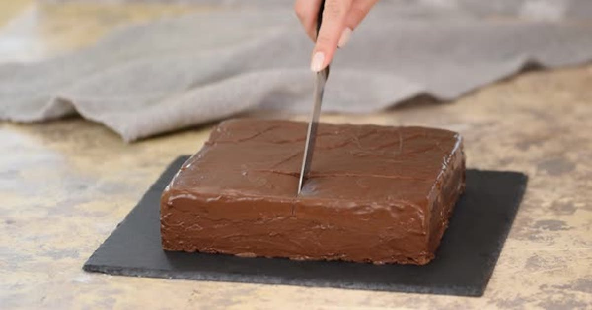 Female Hand Cutting Chocolate Cake with Knife