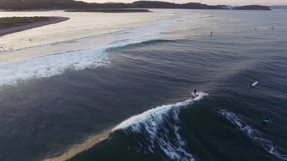 Drone View of Surfers Ripping the Waves in the Sea at Sunset