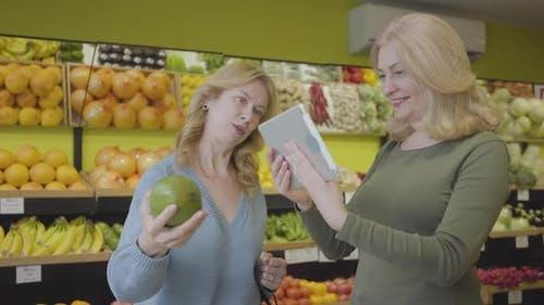Adult Caucasian Women Checking Fruit Origin Using Tablet