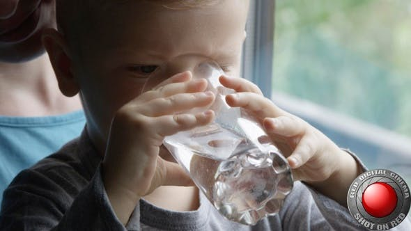 Little Boy Drinking Water From A Glass And Smiling With Mom Holding Him By The Window