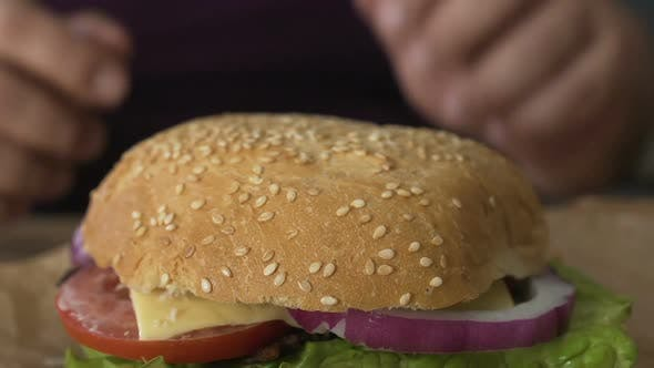 Thumbnail for Man Hands Taking Hamburger With Tomato And Onion From Table, Weight Gain