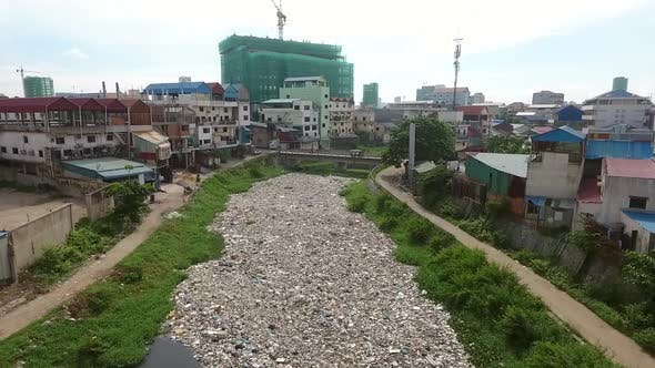 Thumbnail for Aerial view of polluted river crossing neighborhood, Cambodia.