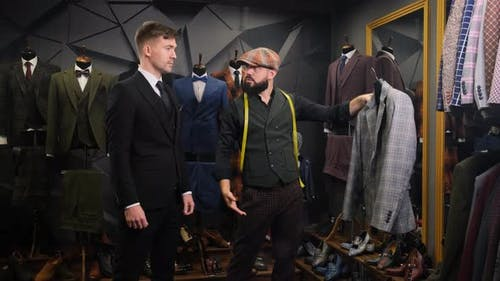 Mature Tailor Helps the Client Choose a Classic Three-piece Suit in an Atelier. Creative Adult