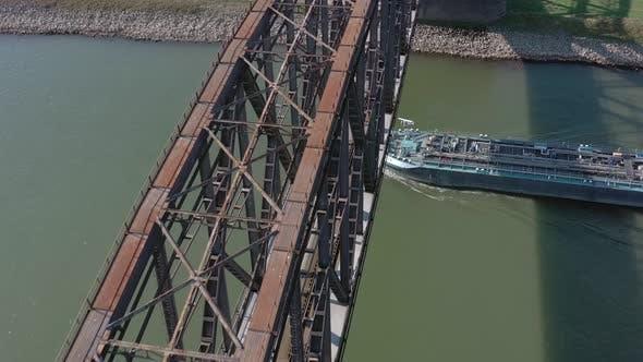 Bulk Carrier Cargo Ship Passing Under An Old Iron Bridge