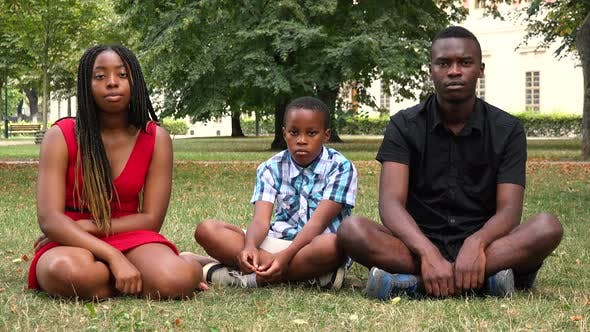 Thumbnail for A Black Family Sits on Grass in a Park and Looks Seriously at the Camera