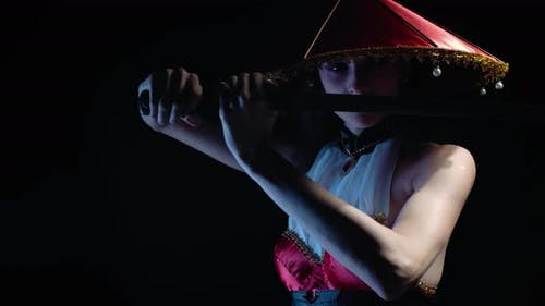 Gorgeous Young Woman with Asian Makeup and a Hat Holding a Katana