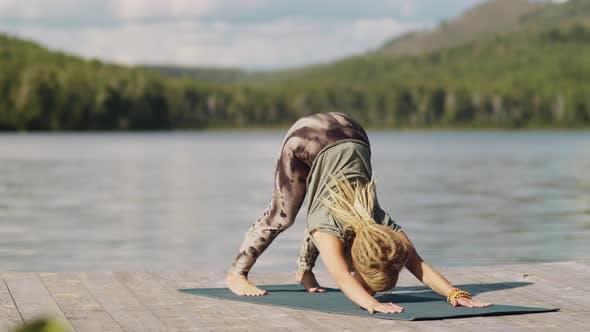 Young Woman Practicing Vinyasa Yoga Outdoors