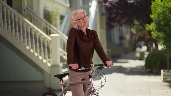 Thumbnail for Lovely senior woman standing with bicycle on quiet street enjoying sunny day
