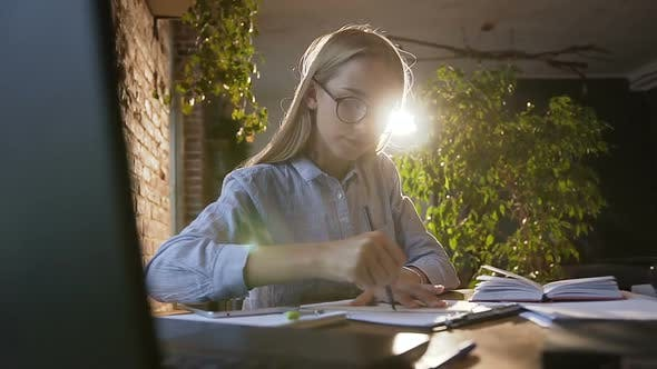Cover Image for Young Engineer Girl Works in a Modern Office with Red Brick wall