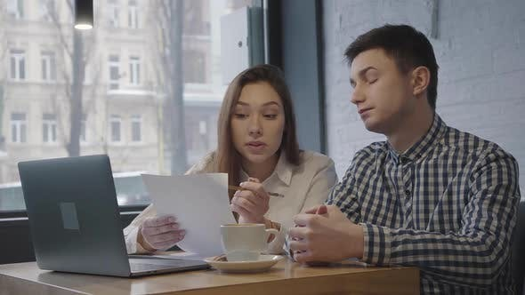 Portrait of a Young Guy and Girl Sitting at a Table with a Laptop Near the Window in a Cozy Cafe or