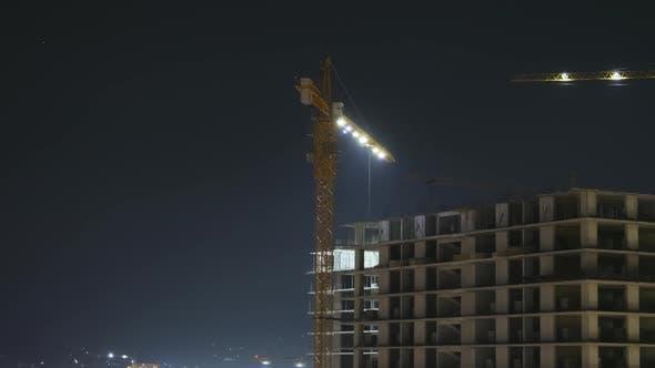 Thumbnail for Gebäudebau bei Nacht. Zeitraffer. Turmkran auf einer Baustelle mit Beleuchtung